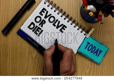 Writing note showing Evolve Or Die. Business photo showcasing Necessity of change grow adapt to continue living Survival Man holding marker notebook clothespin reminder wooden table markers. poster