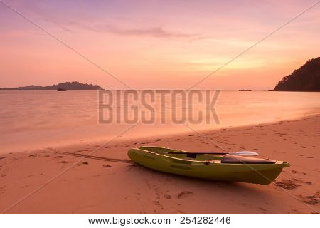 Canoe On The Beach At Twilight Time.
