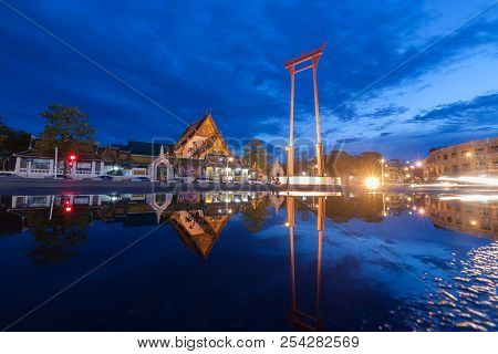 Reflection Of The Giant Swing And Suthat Temple At Twilight In Bangkok, Thailand