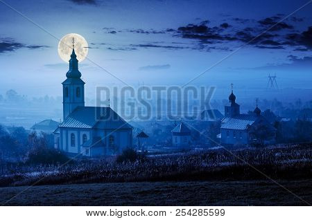 Catholic And Orthodox Churches At Foggy Night In Full Moon Light. Lovely Countryside Scenery In Autu