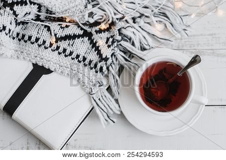 Flat Lay With A Cup Of Red Hibiscus Tea, White Book Or Diary, Lights For Home Decor And Knitted Blan