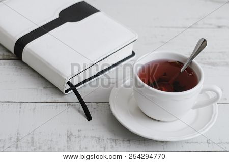 Red Hibiscus Tea And A Book (or Notebook, Diary Or Business Planner) On Wooden Table. Hot Herbal Bev