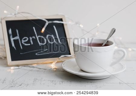Herbal Tea In A White Cup, Lights For Home Decor And Blackboard With Chalk Text