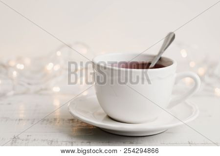 Cup Of Red Hibiscus Tea In A White Mug, Yellow Lights On Background. Herbal Drink On Wooden Table. T