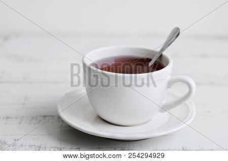 Red Tea In A White Cup On Wooden Table. Hibiscus Drink. Tea Break