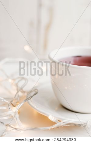 Vertical Photo Of Red Hibiscus Tea In A White Cup And Small Yellow Christmas Lights For Home Decorat