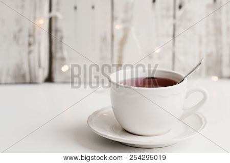 Red Tea In A Small White Cup On White Table, Wood And Small Yellow Lights As Background