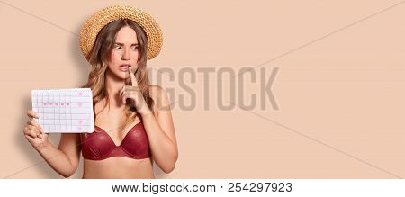 Indoor Shot Of Thoughtful Embarrassed Female Wears Summer Hat And Swimsuit, Holds Period Calendar, T