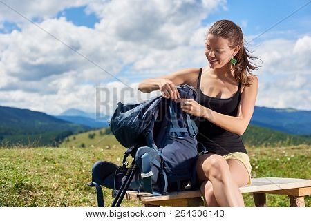 Attractive Smiling Woman Backpacker Hiking Mountain Trail, Sitting On A Wooden Bench On Grassy Hill,