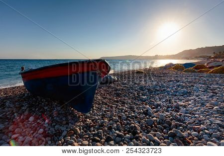Old Anchored Fishing Boat On A Beach Of The Mediterranean Sea. Sunrise On The Mediterranean Sea.