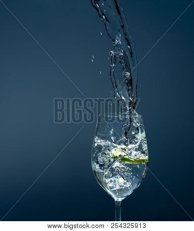 water glass with mineral water and lime for refreshment on hot