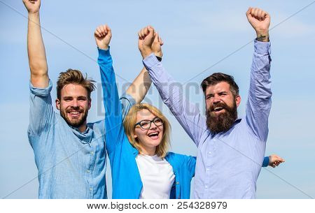 Company Of Three Happy Colleagues Or Partners Celebrating Success, Sky Background. Success Concept.