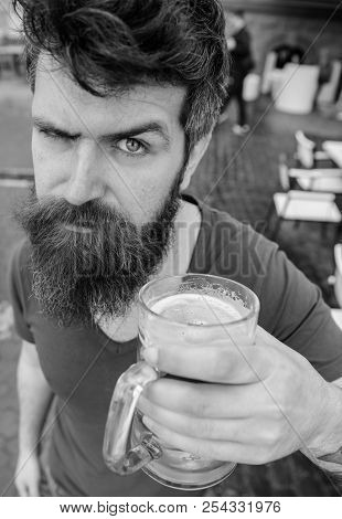 Guy having rest with cold draught beer. Man with beard and mustache holds glass with beer while relaxing at cafe terrace. Hipster on strict face drinking beer outdoor. Draught beer concept. poster