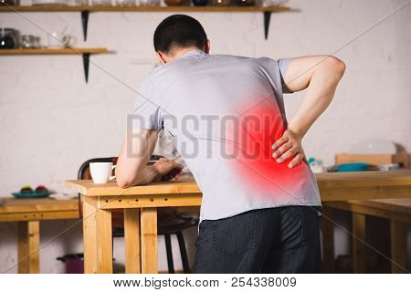 Back Pain, Kidney Inflammation, Man Suffering From Backache At Home, Painful Area Highlighted In Red