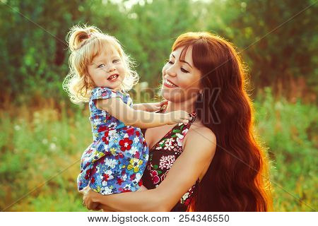 Cute Baby In Her Mothers Arms Outdoors Portrait. Happy Mom And Baby Photography Concept