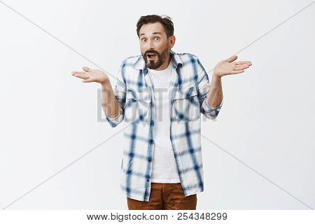 How Should I Know. Unaware Confused Adult Guy With Beard And Moustache In Casual Checked Shirt Over