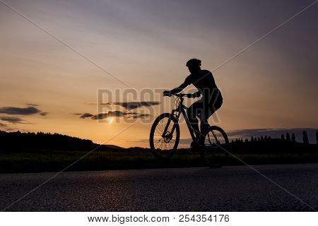 Silhouette Of Boy On The Bike. Young Cyclist Is Jumping On His Bike During Sunset. Fore Wheel Is Ove