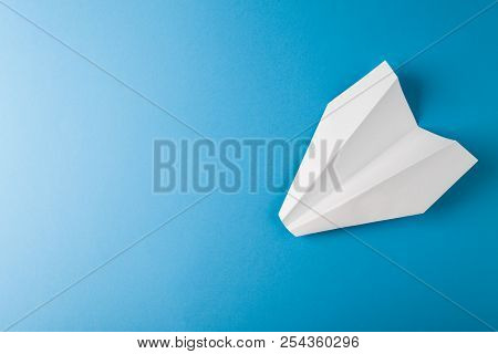 Paper Airplane On A Blue Paper Background