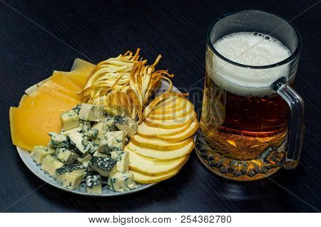 A Glass Of Light Beer Ipa And A Plate Of Sliced cheese Of Different Varieties On A Dark Table
