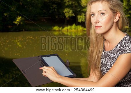Technology, Outdoor Relaxation Concept. Woman Sitting In Park, Relaxing And Using Tablet, Ebook Spen