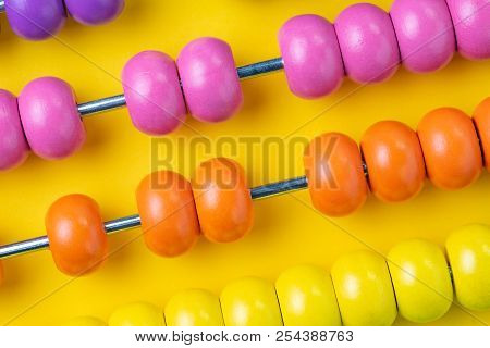 Colorful Wooden Pink And Orange Abacus Beads On Yellow Background, Business Financial Or Accounting