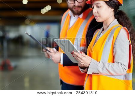 Mid Section Portrait Of Female Factory Worker Using Digital Tablet While Discussing Production With