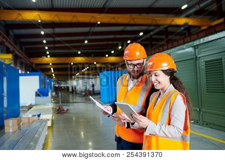 Waist Up Portrait Of Smiling Female Factory Worker Using Digital Tablet While Discussing Production