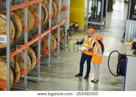 Full length portrait of bearded businessman wearing hardhat and holding clipboard doing inventory in production workshop, accompanied by female factory worker, copy space poster