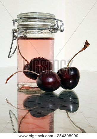 Wild Cherries And Small Glass Jar Of Sweet Cold Compote Against A High Key Background. Selective And