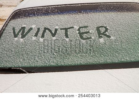 Car With Snow On The Windshield And The Words Winter Written.