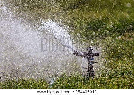 Watering The Grass With The Sprinklers To Keep It Growing