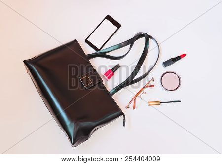Fashion Concept: Flatlay Of Black Leather Bag With Smart Phone, Glasses And Cosmetics On Pastel Back