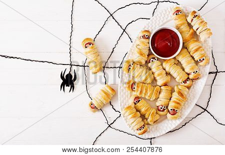 Scary Sausage Mummies In Dough With Funny Eyes On Table. Funny Decoration. Halloween Food. Top View.
