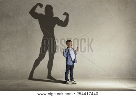 The Little Boy Dreaming About Athletic Bodybuilder Figure With Muscles. Childhood And Dream Concept.