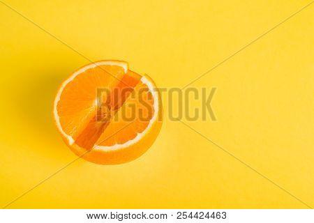 Concept Vitamin С. Fresh orange in pill form Yellow background. Metaphor Minimalism Close-up