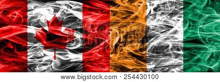 Canada Vs Ivory Coast Smoke Flags Placed Side By Side. Canadian And Ivory Coast Flag Together