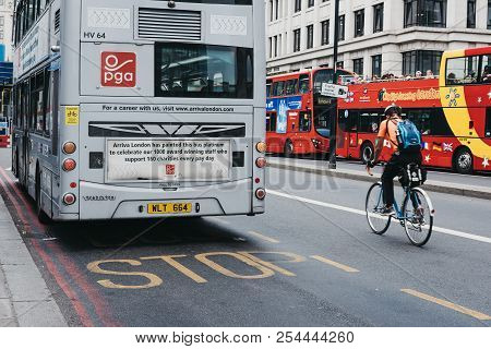 London, Uk - July 24, 2018: Cyclist Going Past A Double Decker Bus On A Street In The City Of London