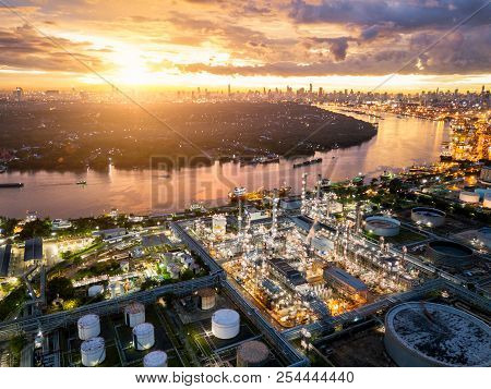 Aerial View Of Oil Refinery Near International Port At Night. Panorama Of Refinery Plant At Sunset.