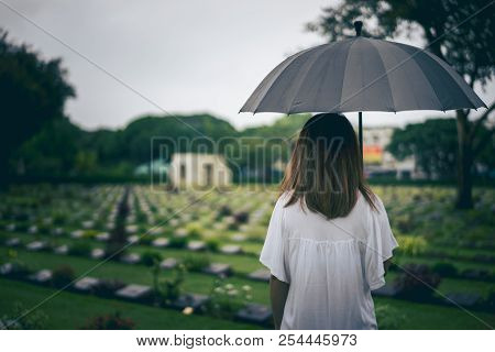 Young Woman Holding Black Umbrella Mourning At Cemetery