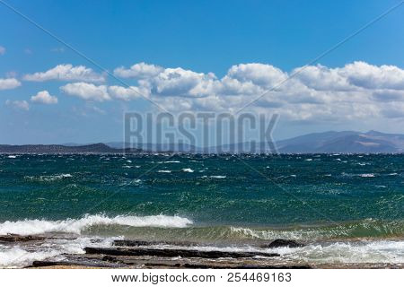 Windy beach and stormy sea, waves splashing on rocks, blue sky with clouds background