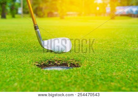 Golf Club And Ball In Grass, Golf Club And Golf Ball Close Up In Grass Field With Sunset.
