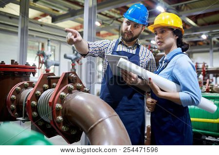 Portrait Of Two Factory Workers Pointing Away While Working With Piping And Machines In Modern Works