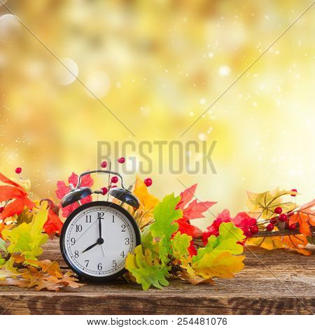 Autumn Time - Fall Leaves With Alarm Clock Over Fall Foliage Background