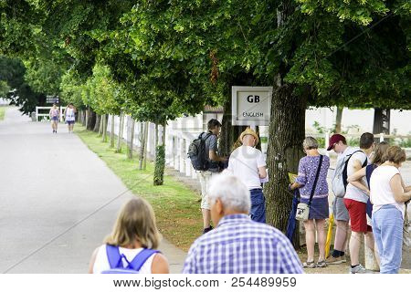 Lipica, Slovenia July 21st 2018. English Tourists Waiting By A Sign Of English Language For A Tour G
