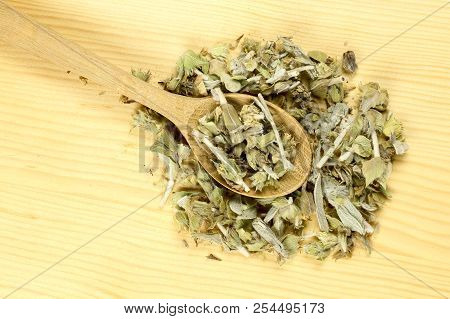 Ladle With Mountain Tea On Wooden Table