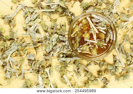 Cup Of Mountain Tea With Tea Leaves On Wood, Top View