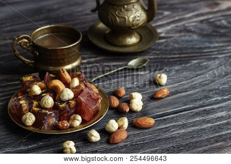 Oriental Arabian sweets with different nuts a cup of coffee. Eastern sweets. Traditional Turkish delight (Rahat lokum) on a wooden background. View from above. poster