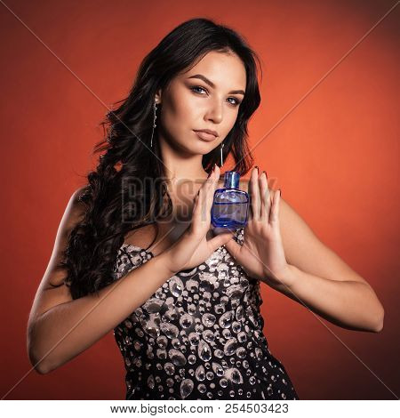 portrait of a beautiful young luxury woman in dress with strass posing with a perfume bottle in blue color looking at camera poster