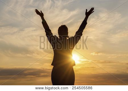 Concept Success In Business. Businesswoman Standing With Arms Raised Against The Sun.