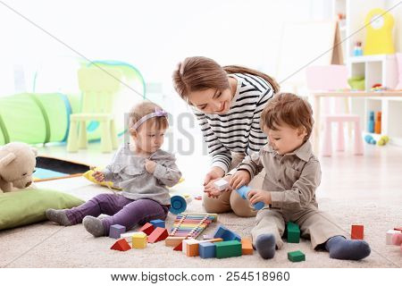 Young nanny playing with little children, indoors